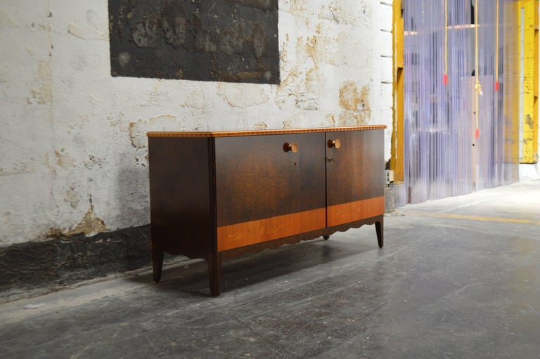 This Swedish Art Deco, verging on art moderne, sideboard server belies that form follows function. In this case, they are considered equals! Crafted in dark flame birch, golden elm and a host of exotic hardwood inlays, this cabinet features intarsia