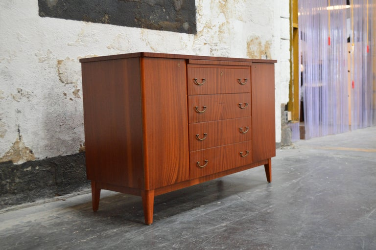 Crafted in ribbon mahogany, this chest/cabinet features a shelf on the left side, five drawers on the right side and four generous drawers down the centre for storage. There is also a pull out shelf on the top for additional serving area. This piece
