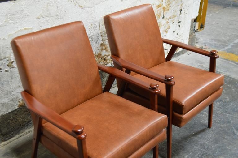 Mid-Century lounge armchairs, circa 1950s. Teak framework and detailed with knobs on the arms. Originally two separate but similar chairs that we have refinished, refined and reupholstered to match. Recently reupholstered in durable recycled leather