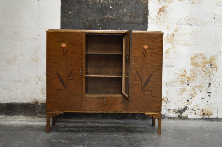 Swedish inlaid Art Deco or neoclassical bookcase or storage cabinet, Sweden, circa 1930s. Exterior dark flame birch. The front two side doors are paneled and inlaid with intarsia of ebonized birch, mahogany, elm and jacaranda wood. The center door
