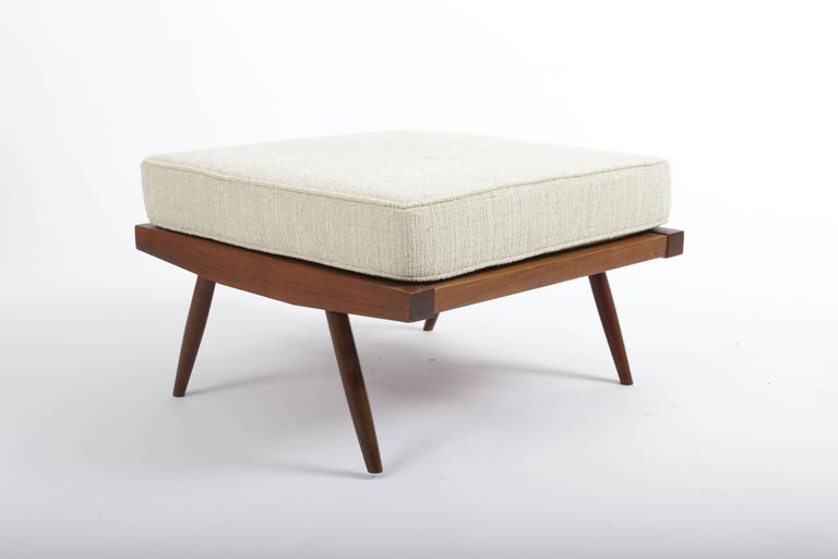 Walnut turned and canted legs supporting walnut framed platform with linen cushion.