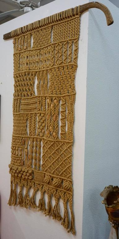 Wall hanging hemp/jute macrame mounted on a weathered plow handle with incorporated ceramic beads.