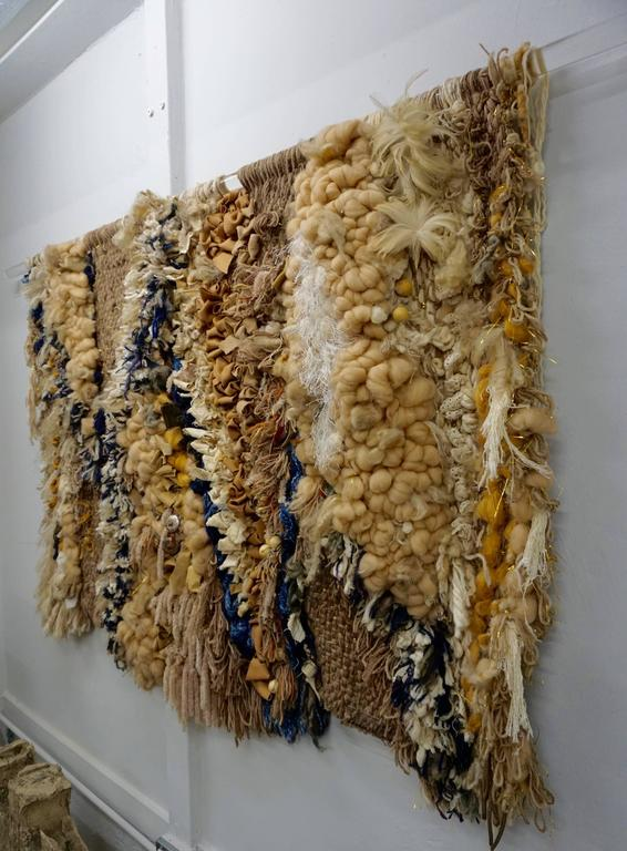 Highly textured with embellishments of leather, wood beads, feathers, lace, tufted wool, rope and conches. Signed by the artist on a piece of Lucite and hung on a Lucite rod.