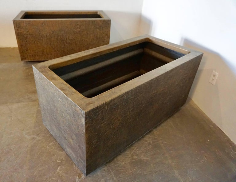 Pair of large, 1970s rectangular planters made by forms and surfaces, Santa Barbara, Ca. They are made of sturdy fiberglass inside with a beautiful Brutalist pattern of bonded bronze on the exterior. For indoor or outdoor use.