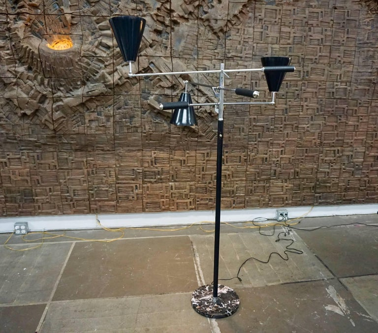 """Sculptural three-armed floor lamp in the style of Arredoluce, Italy. A chromed shaft and adjustable, articulating arms with stitched black leather handles and black metal shades; all seated in a round marble base. Stamped """"Made in Italy"""" at the"""