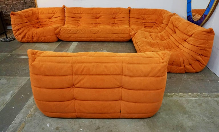 """Five-section modular sofa in orange microfiber ultrasuede. Consisting of one three-seat measuring 67"""" L x 37"""" D x 28"""" H. Two corner pieces measuring 28"""" H x 37"""" D x 37"""" L each and double seaters measuring 47"""" L x 28"""" H x 37"""" D. Excellent overall"""