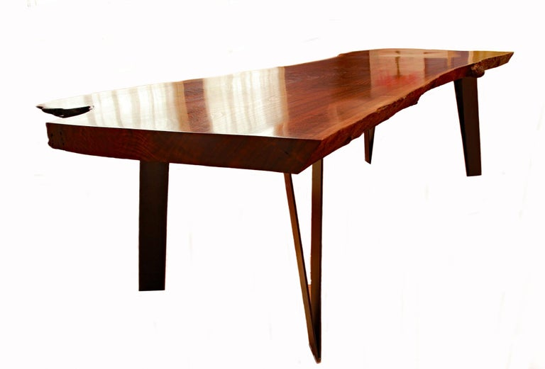 Artist and creator Charles Green is known for his exceptional hand-crafted steel and rare woods custom furniture pieces. This magnificent slab dining table was hand crafted by the artist using a single slab of Claro Walnut, a highly prized wood. The