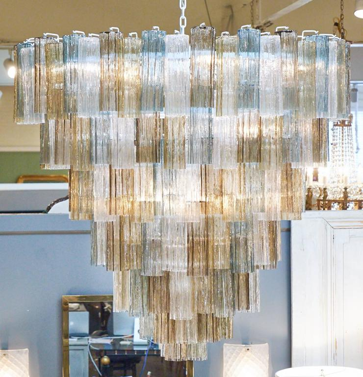 Italian Murano glass chandelier in the style of Mazzega with seven tiers of glass hanging on a white coated steel structure, rewired for the US. Extruded, textured glass in light and dark amber, teal and crystal clear Murano glass, creating a
