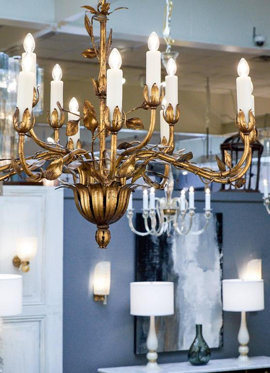 Vintage hand-hammered tole chandelier finished with gold leaf. Two levels with a total of twelve branches with leaf bobeches, adorned with twisting stems and leaves. A refreshing light fixture with a gleaming finish.  Rewired for the US. Height