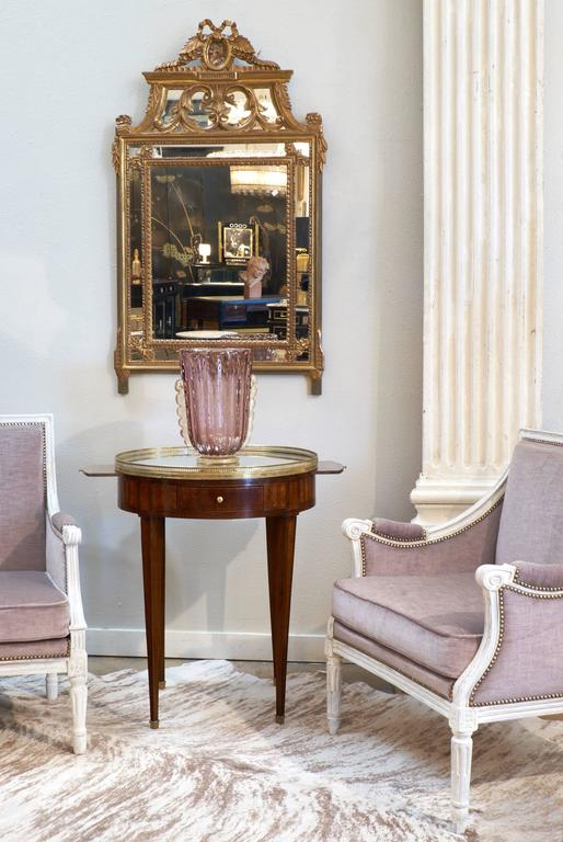 "Lovely French Louis XVI style bergère ""Marquise"" armchair (think antique chair-and-a-half). Original lilac velvet accented with upholstery tacks on hand-carved beechwood frames with a light gray patinated finish. An extra wide seat and plush"