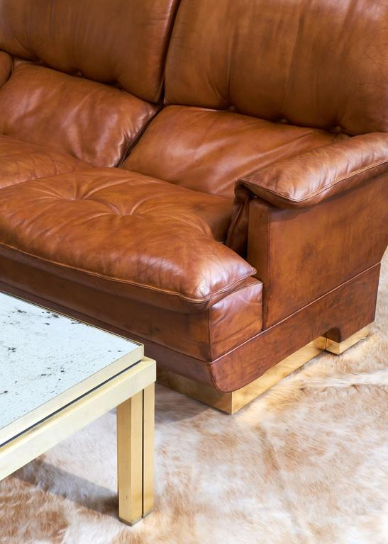 An incredibly comfortable and stylish French vintage leather sofa with brass wrapped base. We love the folded look of the cushions, the warm color, the great feel of the supple, vintage leather and the clean and bold brass base.