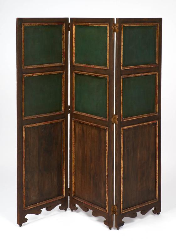 Antique folding screen of three hinged parts fronted with six inset panels of painted scenes framed in gold leaf. Gold leafed wood drapes on red panels ground the piece with a luxurious air, and a wooden frame holds all.