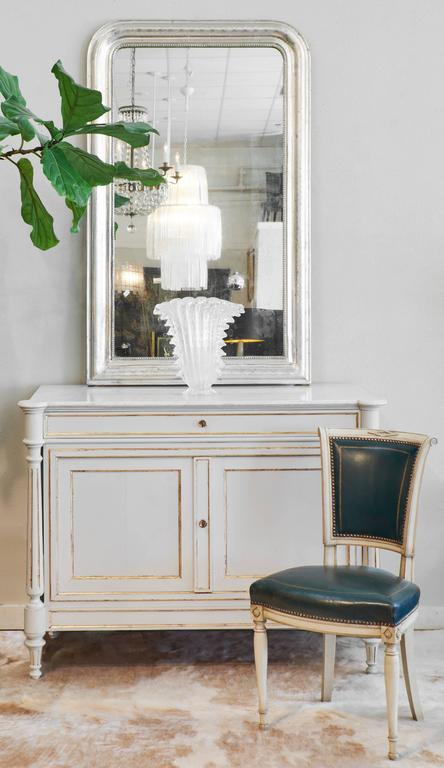 Antique French side chairs include painted wood frames with leather seats and backs. The carved details in the frame make these chairs uniquely eye-catching.