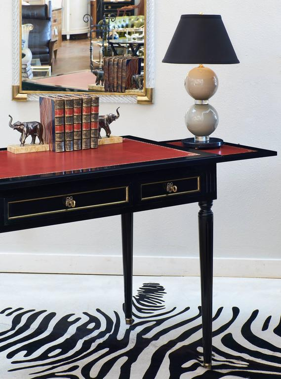 Bureau plat desk in the French Louis XVI style, circa 1940. This elegant writing table has fluted legs, bronze hardware and gilt trim, and three dovetailed drawers. The writing surface is embossed crimson red leather, and covers the two pull-out