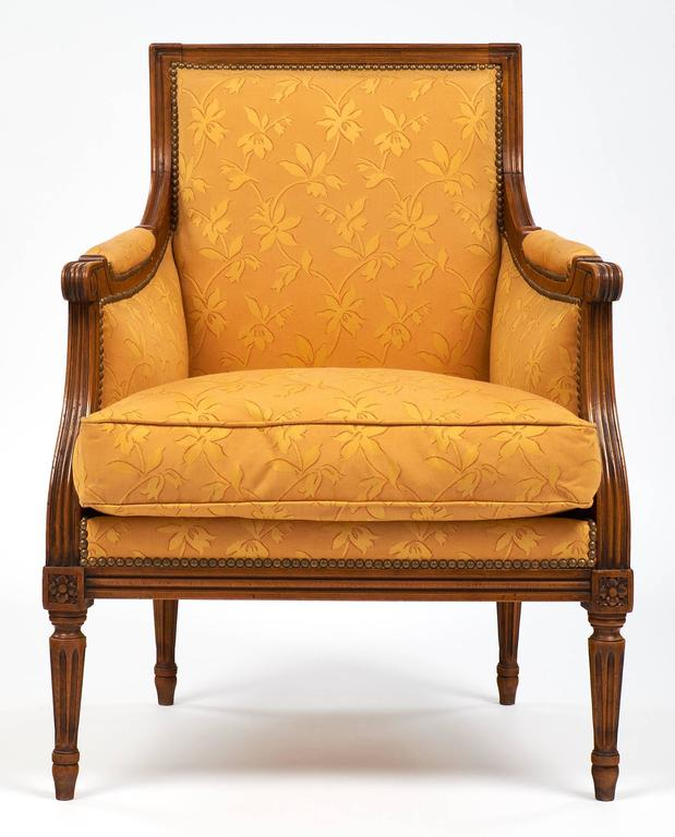 Vintage French Louis XVI style bergères with solid cheerywood frames and complimentary fabric upholstery in a floral pattern. The legs have hand-carved fluting and details! Each chair features a square back and down filled pillows. We love the
