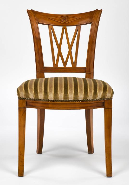 "Comfortable and elegant set of eight dining chairs made of solid cherrywood. The set has the original velvet upholstery that is stamped and in very good condition. The frames are hand-carved and featured a ""rosace"" on the upper apron, front saber"