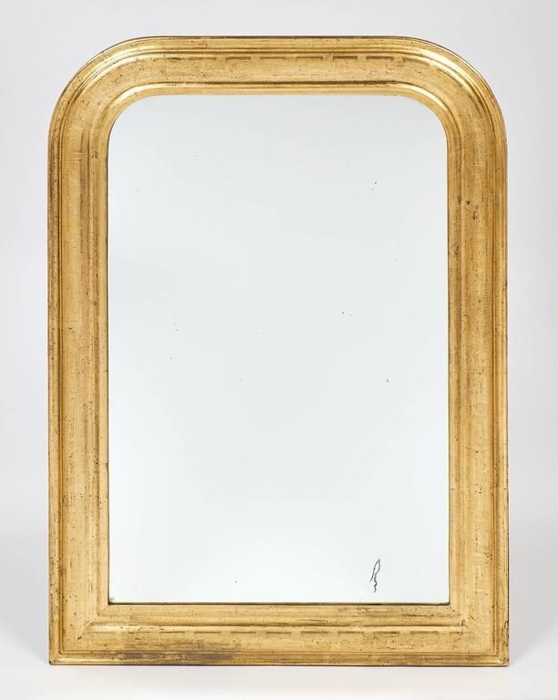 Pair of antique Louis Philippe mirrors with a 23-Carat gold leafing on a sienna glaze. This pair is chiselled with a Greek key frieze. The mirrors are original.