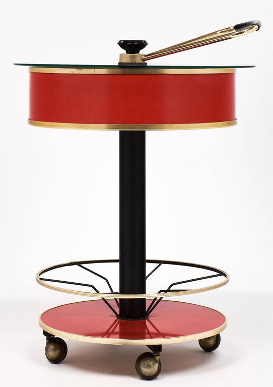 A circular bar cart with whimsical features such as a central leg and a hydraulic system for opening the case using the brass handle. At the raised position, the glass top lifts allowing access for glasses to be stored in the space within. Bottles