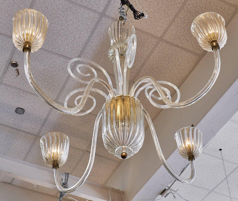 A stunning Seguso chandelier from the island of Murano. Made of hand blown glass with 23 karat gold flecks in the glass. The spectacular fixture boasts four branches and ridged cups, along with large scrolls and a bold main stem design. We loved the