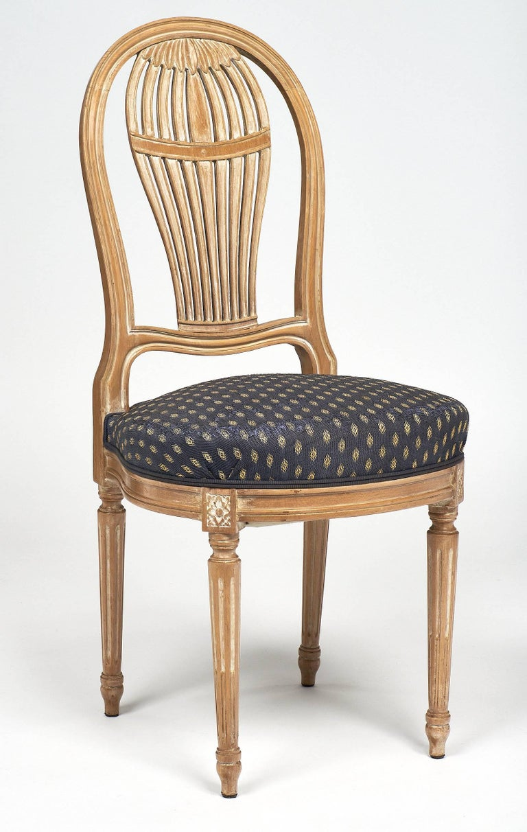 Beautiful set of six dining chairs in the Louis XVI style. These chairs have large circular seats with a strong back inspired by the shape of 18th century hot air balloons. They are made of beech wood with a light céruse finish. We love the elegant