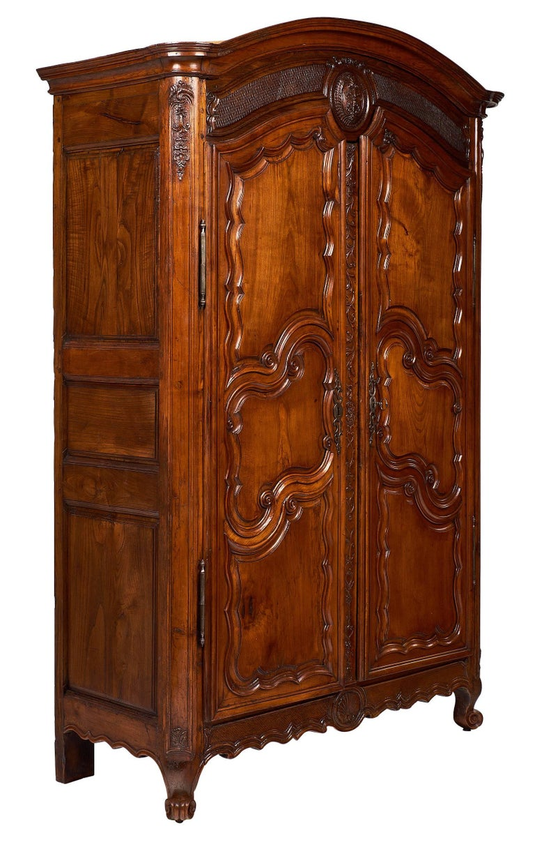 "An impressive, hand-carved armoire of rich and figured honey-toned walnut. It features a ""policeman hat"" shaped cornice and the original cabriole legs with feet ""a l""escargot"". This stunning cabinet presents a rich array of hand-carved and chiseled"