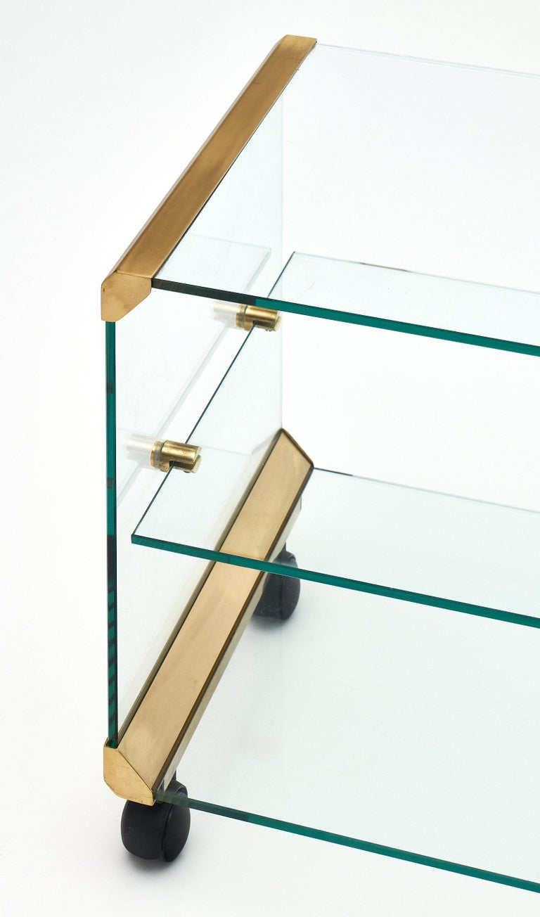 Italian modernist glass and brass side table with one glass shelf and supported by casters. The glass structure is held together with the original brass hardware and corners. We love the unique style and quality of this piece.