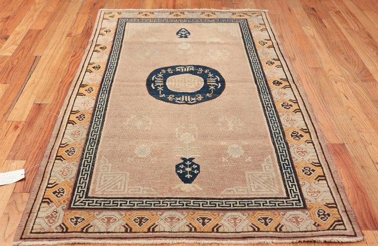 Antique Khotan rug, country of origin: East Turkestan, circa 1900. Showcasing delicate shades of sepia and cream, this Khotan carpet stands out for its skillful use of beautifully detailed borders. The work features interlocking Greek key designs in