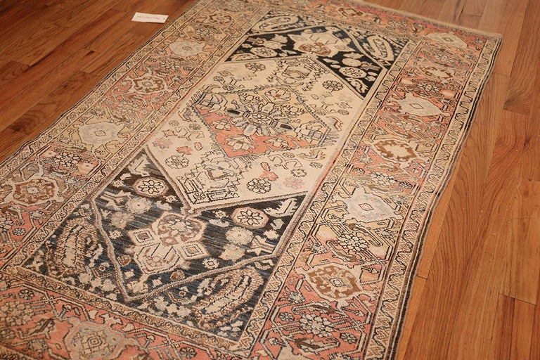 The central banner of this antique Persian rug is formed of nested diamonds cut off on the outer corners. The focal figure on this Malayer is backed in orange and yellow, featuring white flowers sprouting radially, each stitched with thin black