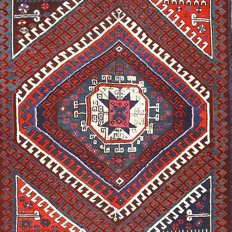 This medley of dark blue with shades of red, accented by bright white, forms an attractive tribal antique Bergama rug from Turkey. The rectangular, antique rug features a dark blue central area packed with several shapes, triangles and diamonds