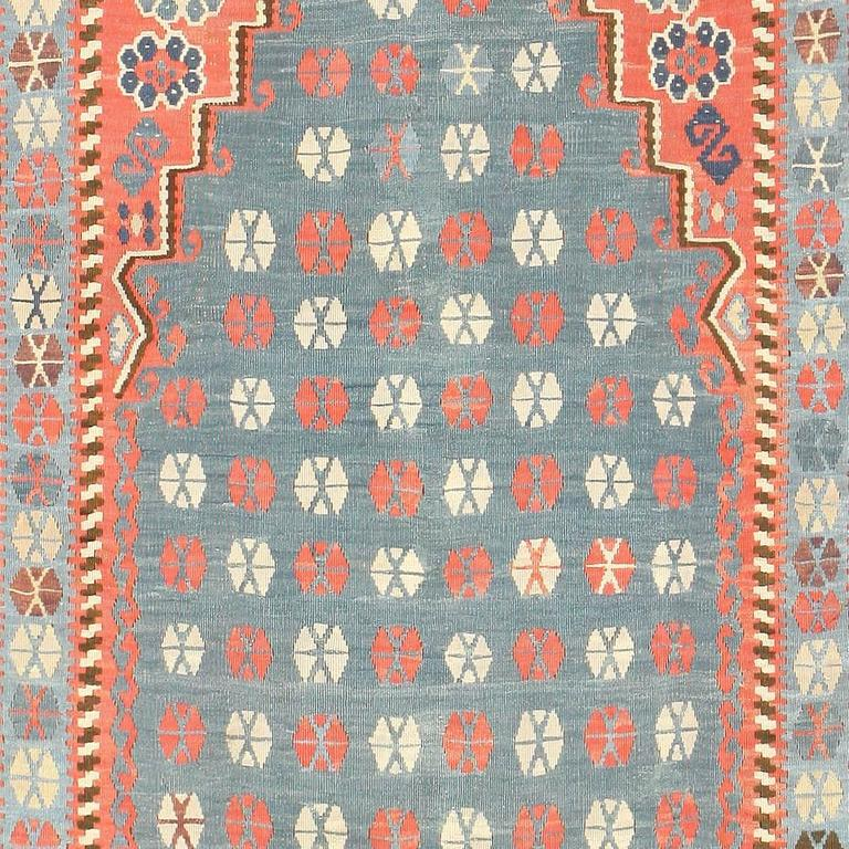 This Kilim rug uses powerful colors to create clear interest points of interest. From forest green to fire red, there are numerous cool and warm tones that complement the presence of the beige at the background. This results in a strong transition