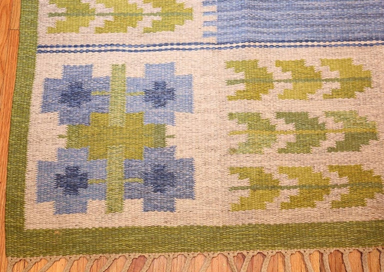Vintage Swedish Kilim by Berit Woelfer, Sweden, Mid 20th Century —  Size: 6 ft 6 in x 9 ft 2 in (1.98 m x 2.79 m)  Simple in its color scheme and overall presentation, this charming carpet relies on angular shapes and patterns to convey the setting.