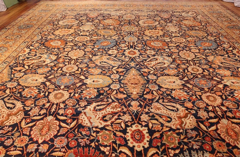 Magnificent oversized navy blue antique Persian Tabriz rug, country of origin / rug type: Persian rug, date circa 1900. Antique Persian Tabriz rugs are world-famous carpets from what is modern day Iran. The Persian city of Tabriz has long been a rug
