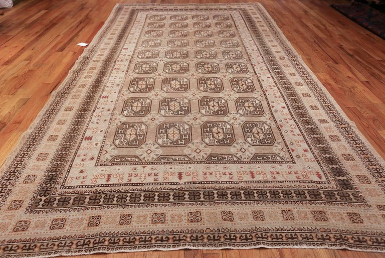 Woven in Khotan, this unique carpet features a classic Tauk Nuska gul motif pattern framed by symbolic borders woven in a combination of earthy neutrals and brown.