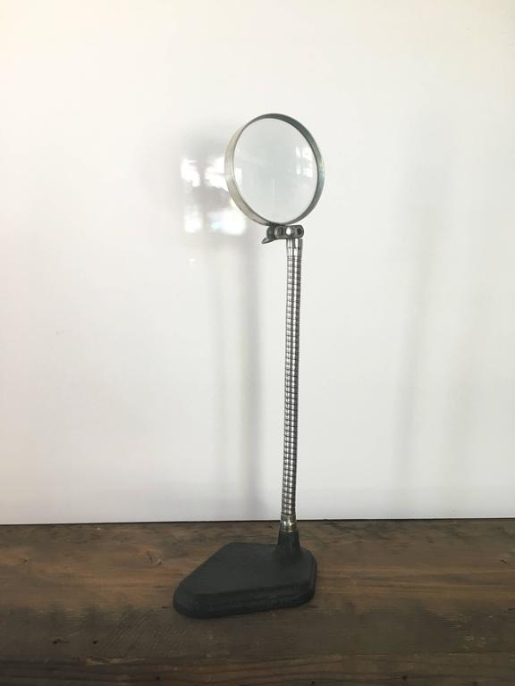 Free-standing vintage magnifying glass. American, circa 20th century. Curving articulated arm on pebbled black base.