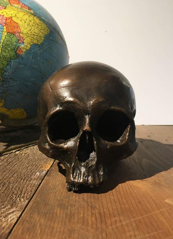 Cast bronze skull. Approximately 10 pounds; heavy enough to be used as a book end or large paperweight in library or office.   Pictured with bronze skull with silver patina.