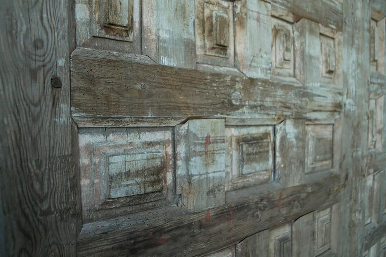 Monumental vintage wooden doors with carved bevelled coffers. 