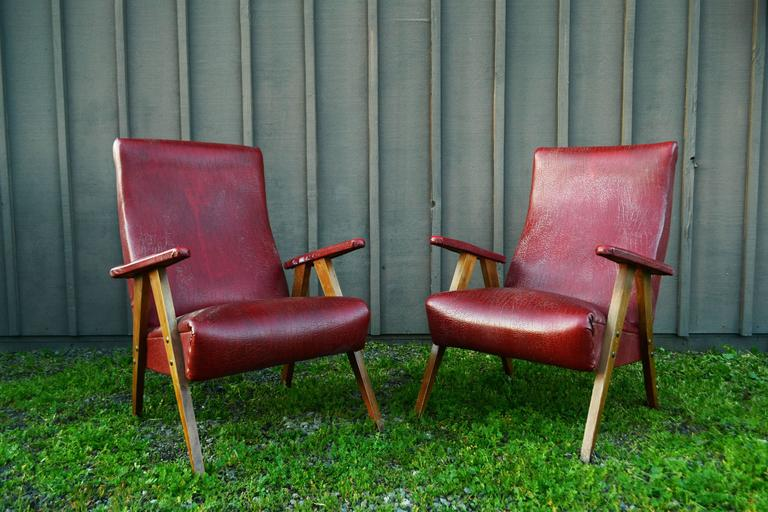 Pair of vintage red leather armchairs with wooden legs and upholstered arms.
