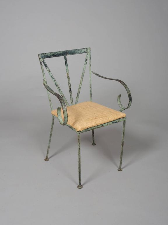 """Set of four beautifully patinated Mid-Century steel garden chairs. Two chairs are covered with cotton, two chairs with rattan. Could be reupholstered at an extra charge. Side chairs: 16.25 seat width, 16.5"""" seat depth, 17.75"""" seat"""