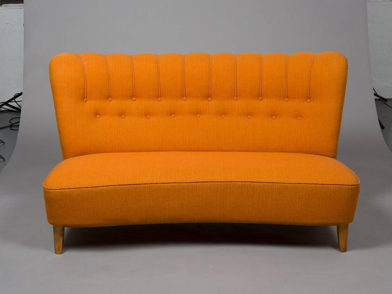 Stylish, Midcentury Danish armless settee with birch legs and button tufting. Upholstered in an orange textural fabric. Matching pair of chairs available. Seat depth: 20.5
