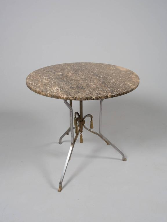Elegant round steel occasional table with gold accents and variegated brown marble top. Attributed to Jansen.