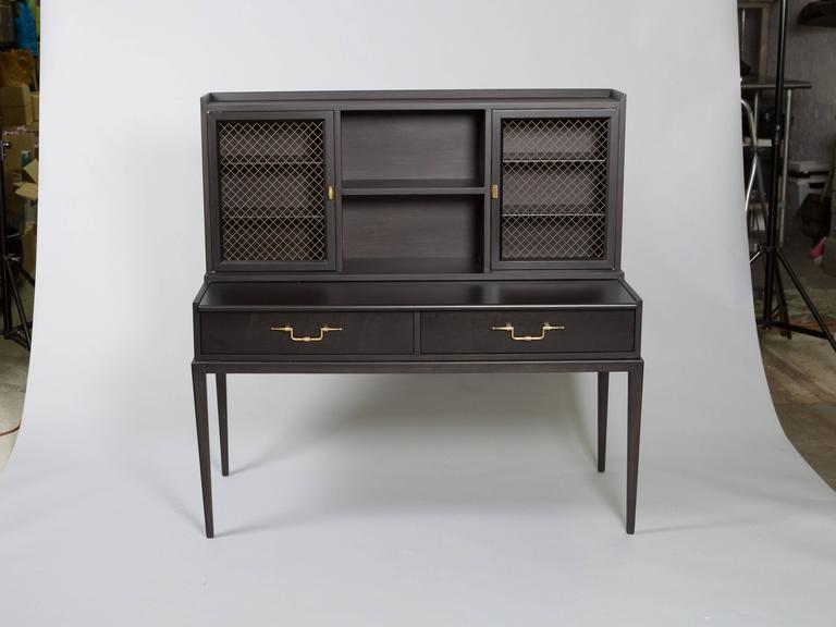 Tommi Parizinger secretary/desk with metal grill doors, brass hardware and tapered legs. Stamped on the inside of drawer. Beautiful restored condition.