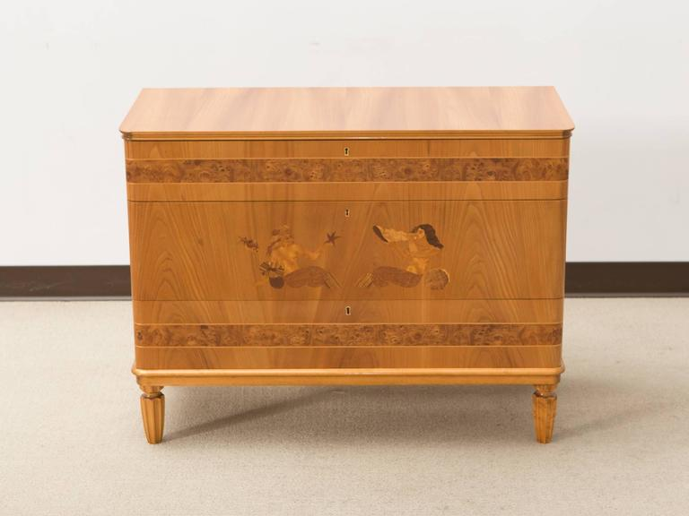 Art Deco three-drawer Danish commode with inlaid nautical imagery and burl wood details and tapered and fluted legs.