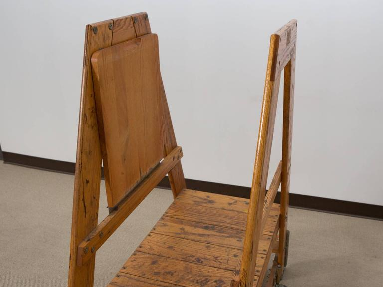 "Mid-20th century, American Industrial oak rolling step ladder stamped ""Bell System"" with folding top step and four metal casters. Very solid construction with great patination."