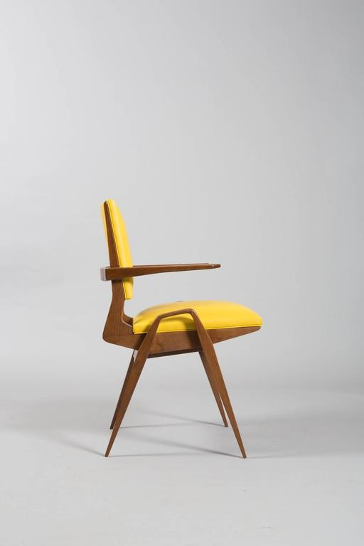 """Set of four architectural French Mid-Century armchairs newly restored and reupholstered in pop shades of citron and bright yellow leather. Measures: Arm height 24 5/8' Seat depth 16.5"""" Seat width 16.75""""."""