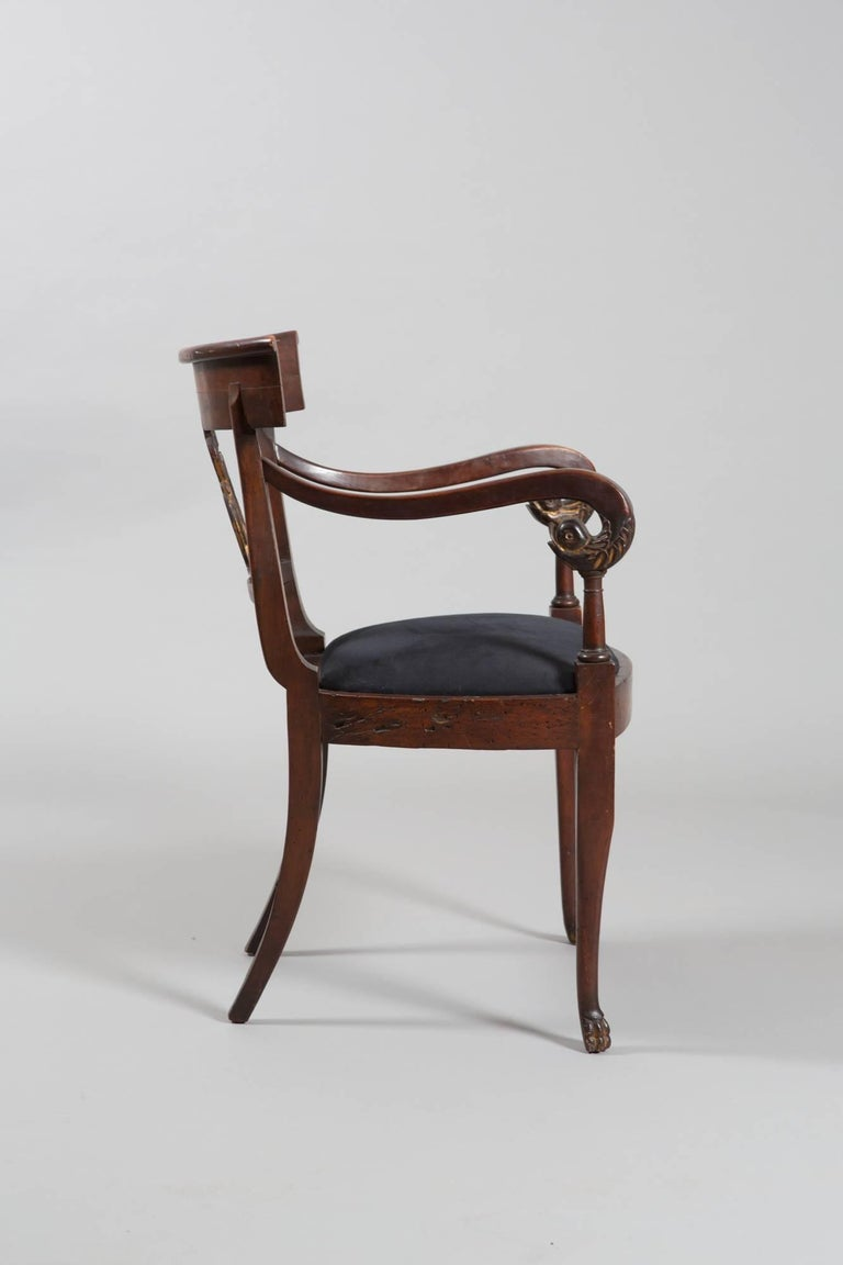 Beautifully carved Directoire style armchair with gilded details on arms, feet and back. Carved backrest with carved swan detail. Very handsome piece!