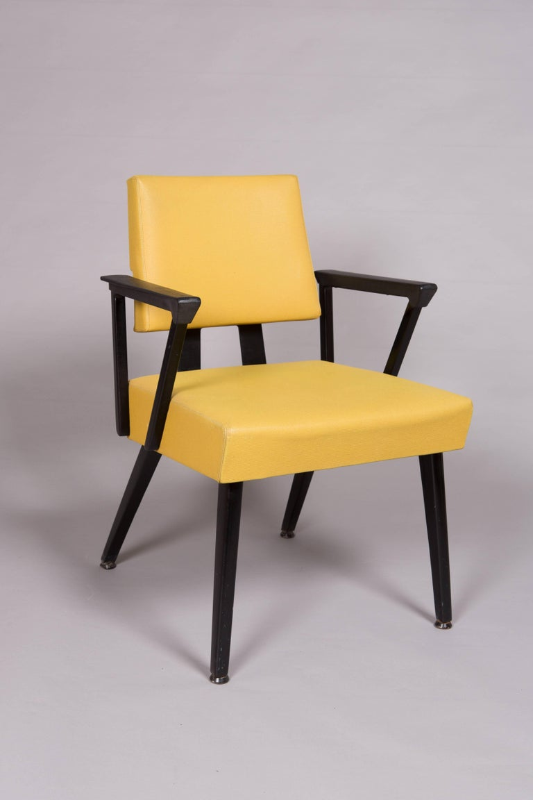 Completely original pair of yellow and black vinyl covered midcentury armchairs with metal frame and faux wood grain detail to arm rests. Very sturdy and comfortable chairs. Great condition considering their age!