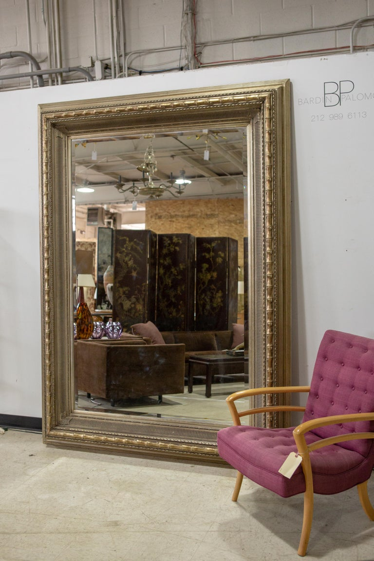 Monumental Neoclassical style metal mirror - Very large (over 7.5' H) , custom made, burnished metal leaf, Neoclassical style mirror with linear and bamboo details throughout. Mirror and frame are in amazing condition. Photo with chair for scale.