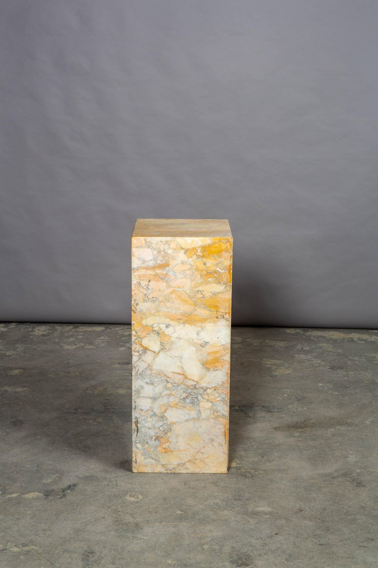 Mid-Century Modern Italian marble pedestal. Heavy and in very good condition, this pedestal has great color variation ranging from ochre to grey with great shades of tan and light browns. Very minor losses to the top edge but consistent with age.