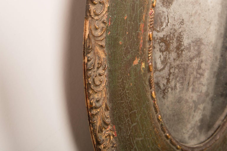 Pair of gorgeous 19th-Century antique oval mirrors with unbelievably beautiful patination to the original mirror. Faded gilt on the edge carving detail, and a wonderful shade of deep green. Some losses and chipping throughout. These mirrors have age