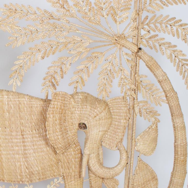 Folky Mario Torres three-panel folding screen or wall hanging made with a metal frame wrapped with wicker or reed and depicting an elephant with palm trees and flowers.